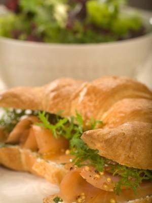 Croissant z kolorowymi sałatami, twarogiem ziołowym i plastrami wędzonego łososia norweskiego