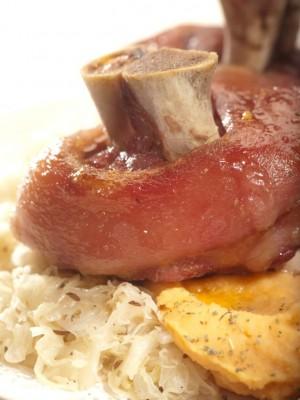 Pieczona golonka wieprzowa podana na puree z grochu z majerankiem i kwaśną kapustą z kminkiem