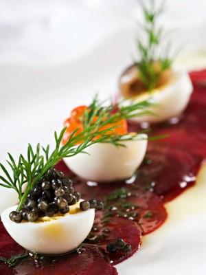 Pieczone plastry buraczków podane z jajkami przepiórczymi, anchois, kawiorem, emulsją pietruszkową i serem bundz