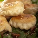 Pierogi nadziewane mięsem kaczki podane z sałatą rukola, suszonymi pomidorami oraz sosem miodowo-balsamicznym